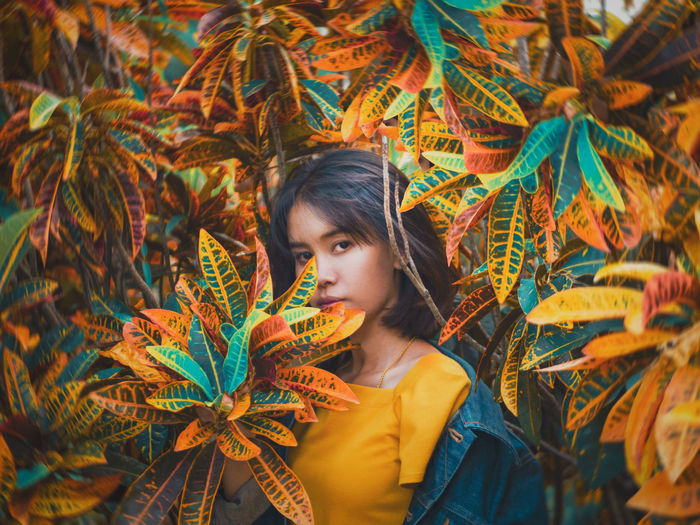 Portrait of woman standing by plants during autumn
