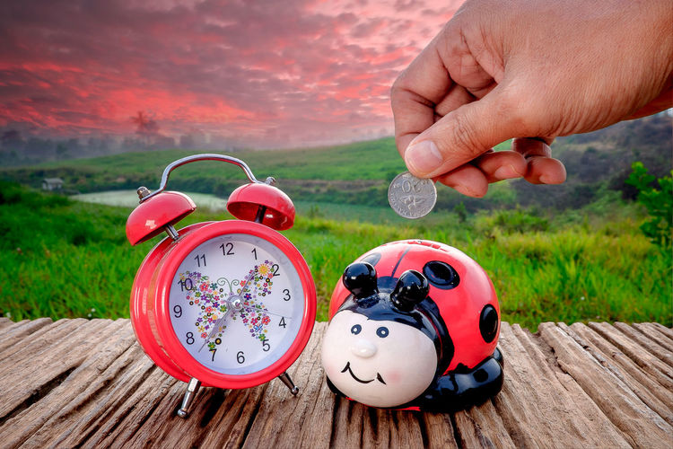 Cropped hand inserting coin in piggy bank by alarm clock on table against sky during sunset