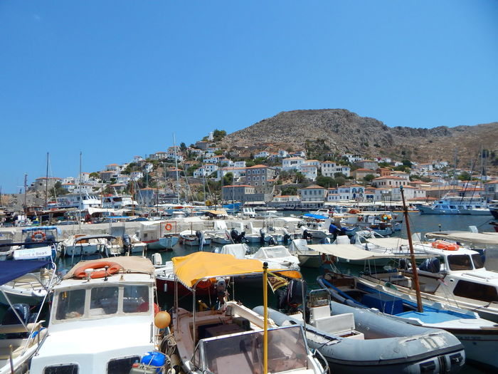 Boats moored on mountain against clear blue sky