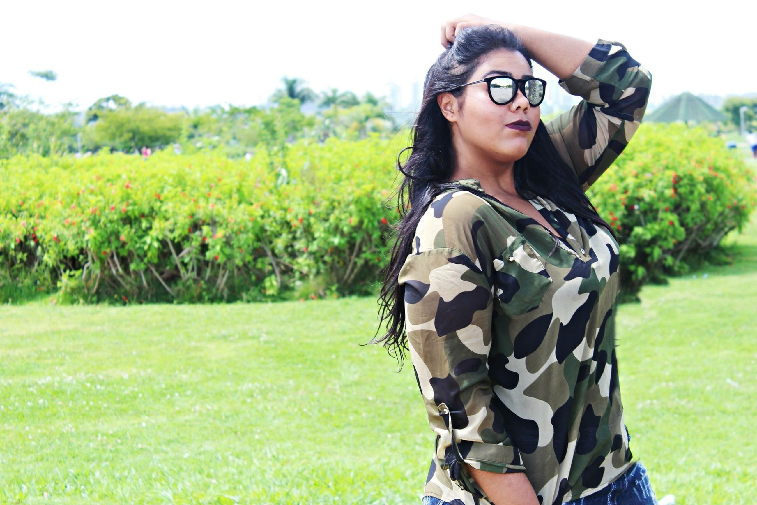 grass, young adult, field, lifestyles, grassy, person, looking at camera, leisure activity, portrait, green color, young women, casual clothing, sunglasses, front view, smiling, three quarter length, standing, tree