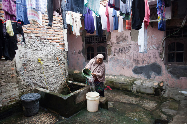 Woman filling water in bucket while standing in alley by buildings