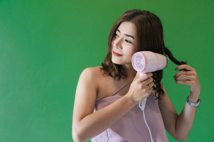 Mid adult woman drying hair with dryer against green background