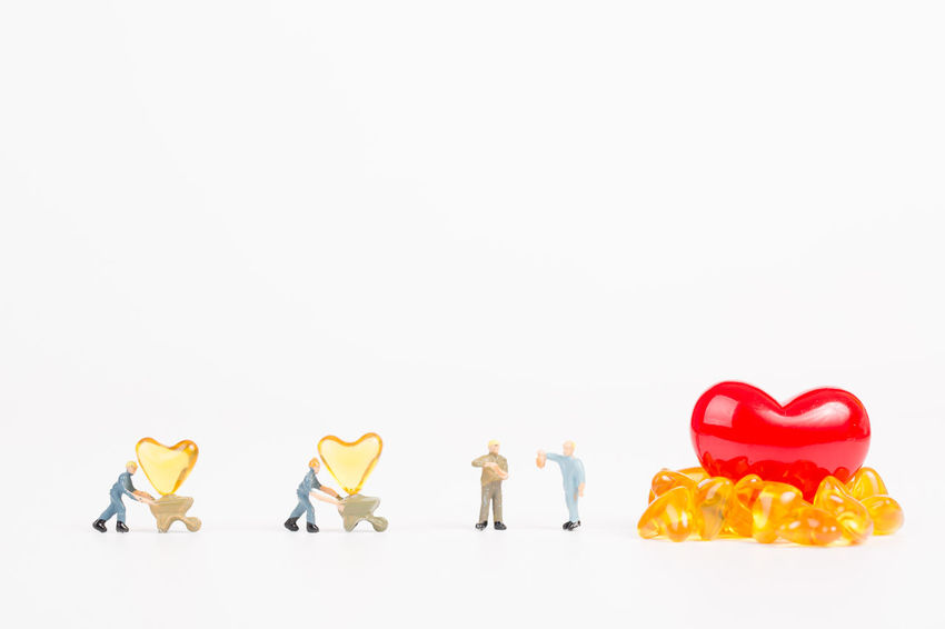 miniature people with cod liver oil on white background Care Doctor  Drug Hospital Teamwork Working Close-up Cod Liver Oil Concept Copy Space Figurine  Healthy Heart Shape Illness Miniature People Phamaceutical Phamacy Pill Small Studio Shot Toy Treatment White Background