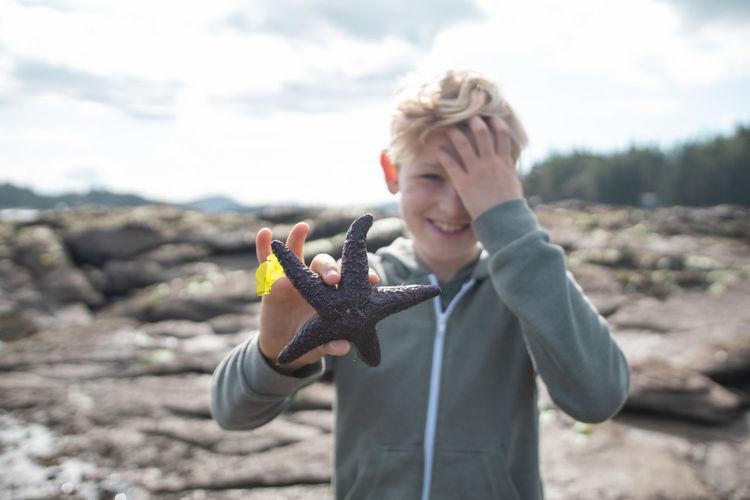 Boy holding starfish at beach