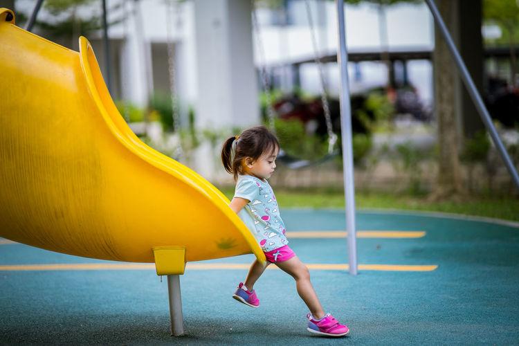 Side view full length of girl playing on slide