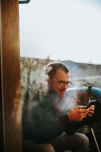 Man using mobile phone while smoking electronic cigarette
