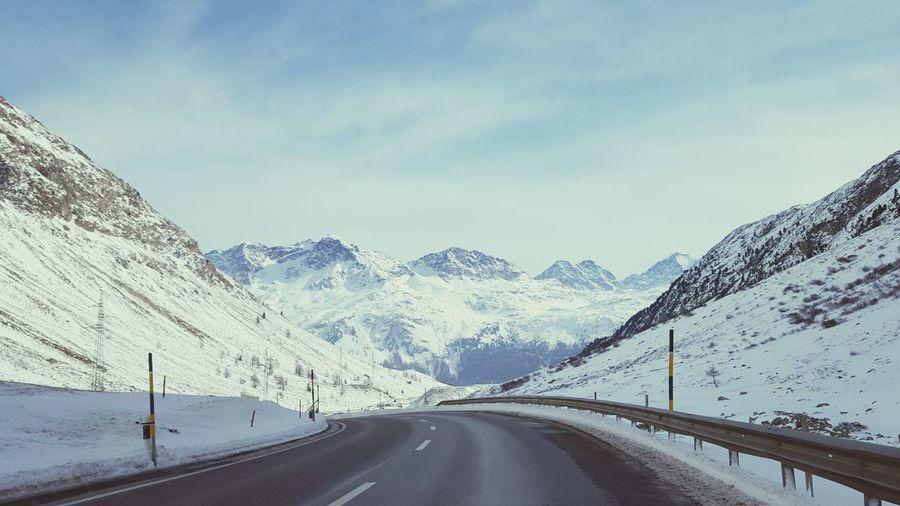 Empty Road Through Snow Mountains