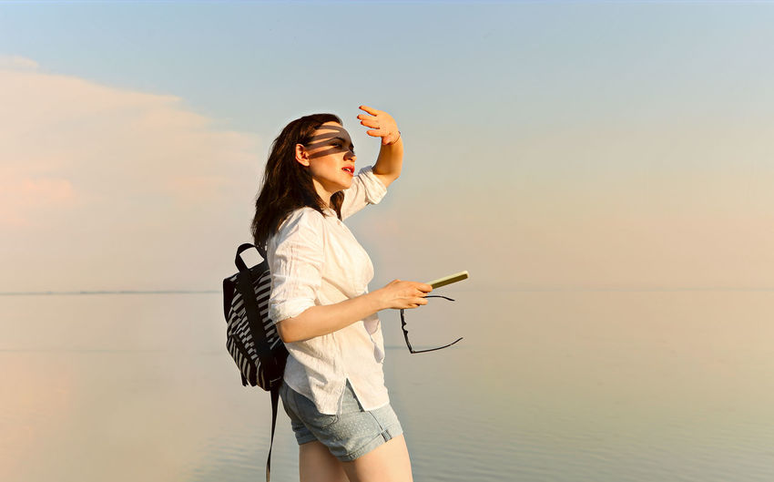 Young woman using phone while standing on sea against sky