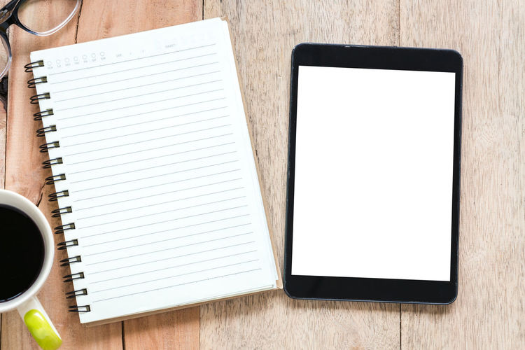 Directly above shot of digital tablet and spiral notebook on table