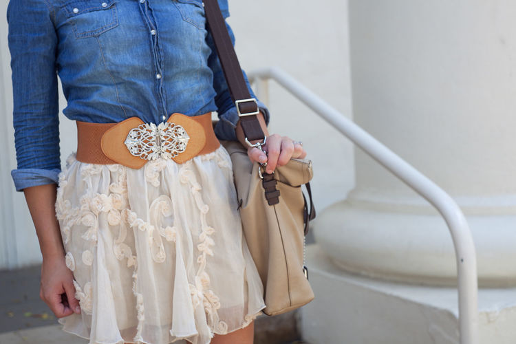 Country singer Fashion Look Buttoned Shirt Denim Blouse Vintage Vintage Fashion Vintage Look Leather Cream Color Skirt Lace Skirt Lace Handbag  Holding Buckle Oversize Wild West American West Street Fashion Young Woman Midsection Woman Denim Shirt Handbag  Belt  Fashion Cowgirl