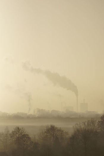Smoke emitting from factory against clear sky