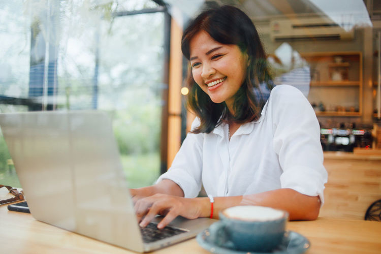 Asian  Background Beautiful Beauty Business Cafe Coffee Color Communication Computer Connection Desk Digital Female Girl Happy Holding Home House Internet Lady Laptop Lifestyle People person Phone Portrait Room Shop Sitting Smartphone Smile Smiling Technology Thinking Vintage Woman Women Work Working Young