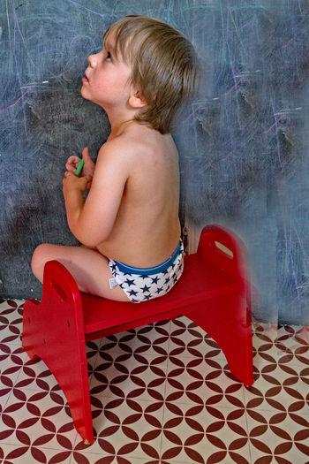 Blackboard Boys Casual Clothing Child Childhood Hairstyle Home Interior Indoors  Innocence Leisure Activity Lifestyles Looking Away Males  One Person Real People Seat Shirtless Sitting Three Quarter Length