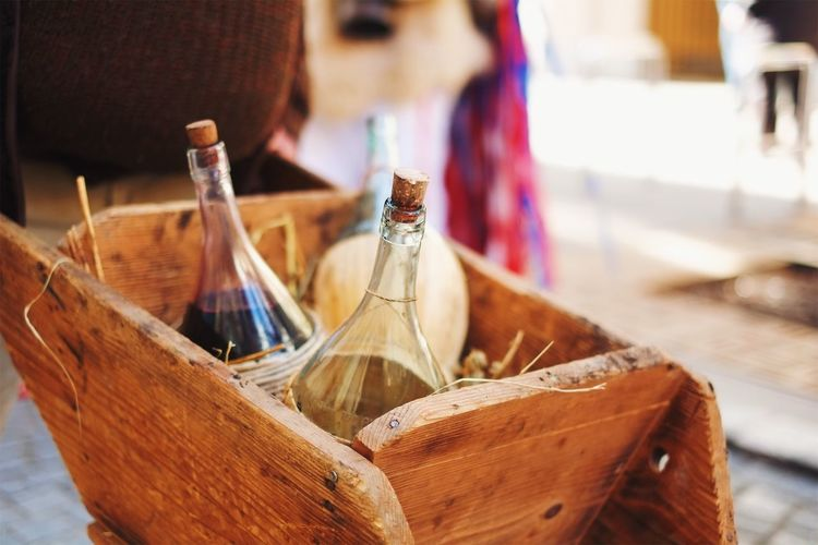 Close-up of alcohol bottles in wooden box