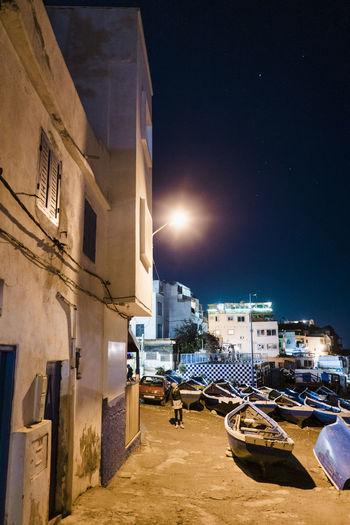Buildings by street against sky at night