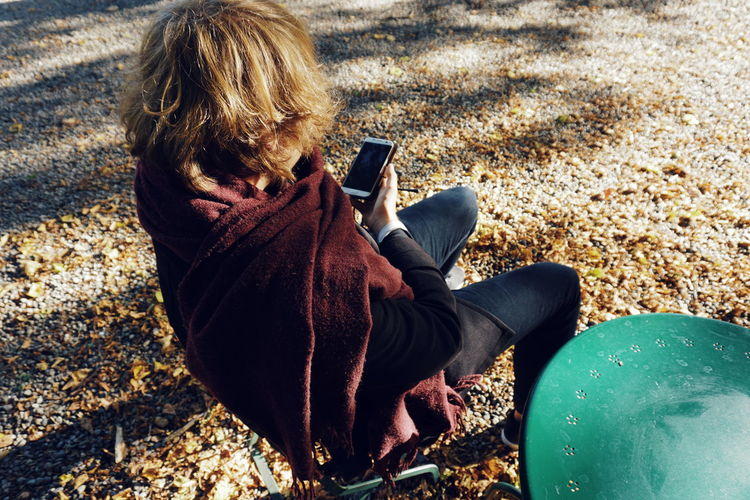 High angle view of young man using mobile phone while sitting outdoors