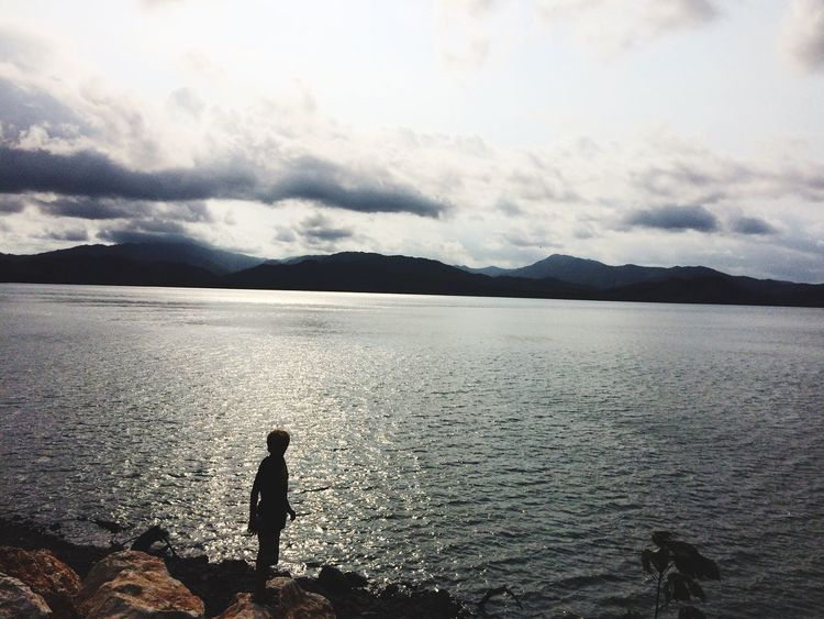 Water Beauty In Nature Nature Real People Sea Scenics One Person Tranquility Tranquil Scene Standing Sky Mountain Outdoors Leisure Activity Silhouette Cloud - Sky Day Childhood Full Length People Lilbro