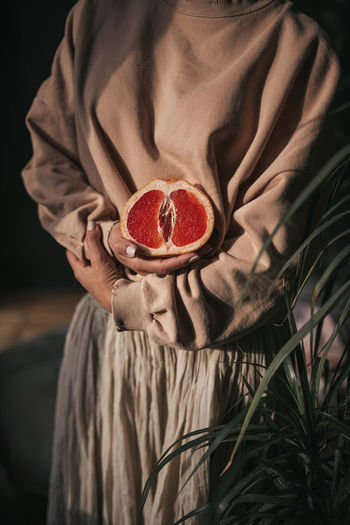 Close-up of woman holding red fruit