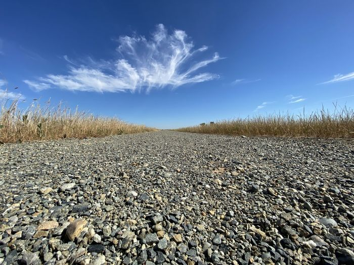 Surface level of stones on land against sky