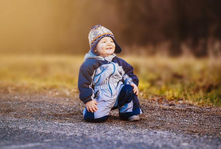 Cute boy kneeling on road
