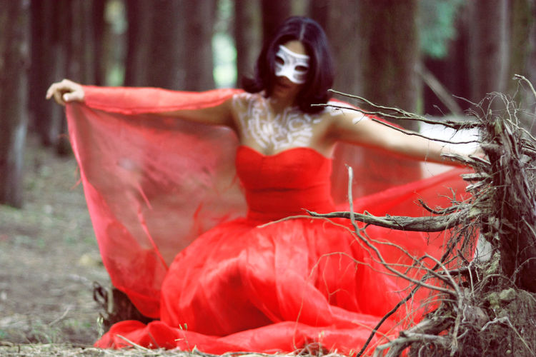 Woman wearing mask against trees at forest