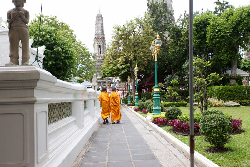 Rear view of monks walking on footpath at temple