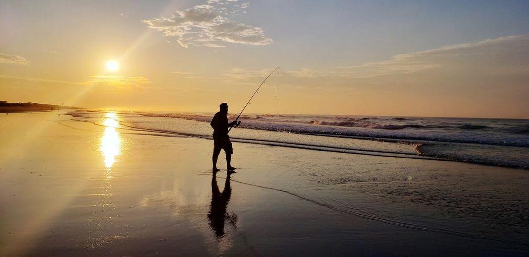 Silhouette man fishing at beach during sunset