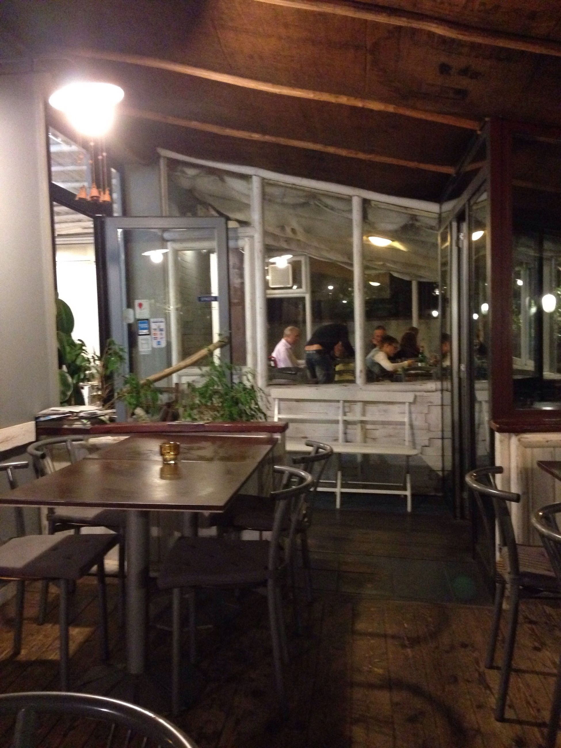 indoors, table, sitting, restaurant, lifestyles, chair, leisure activity, men, person, food and drink, window, glass - material, cafe, sidewalk cafe, casual clothing, dining table, home interior