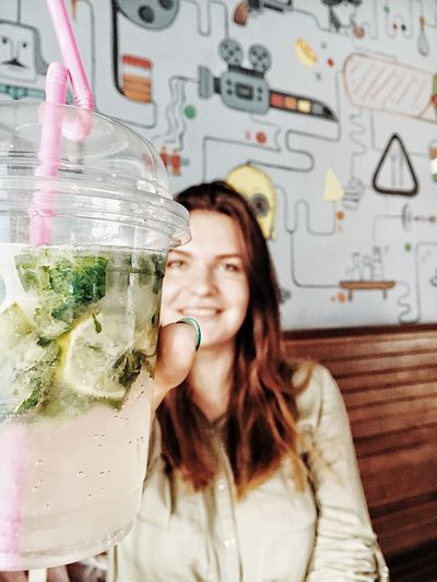 Portrait of smiling young woman holding lemonade in restaurant