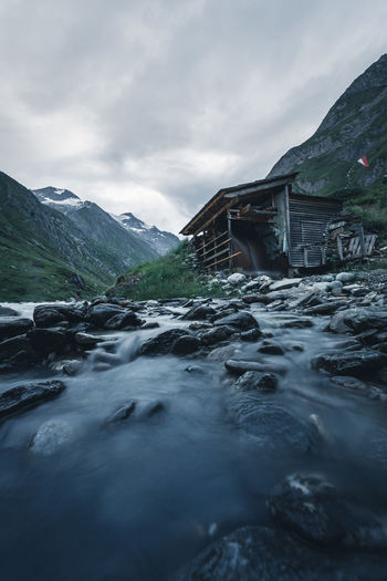 Scenic view of stream by house against sky