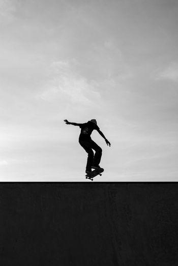 Full length of man skateboarding against sky