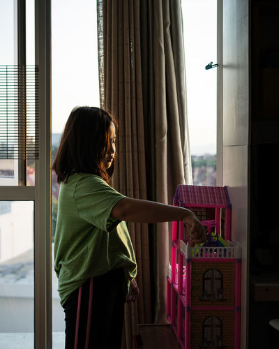 Side view of woman standing by window at home