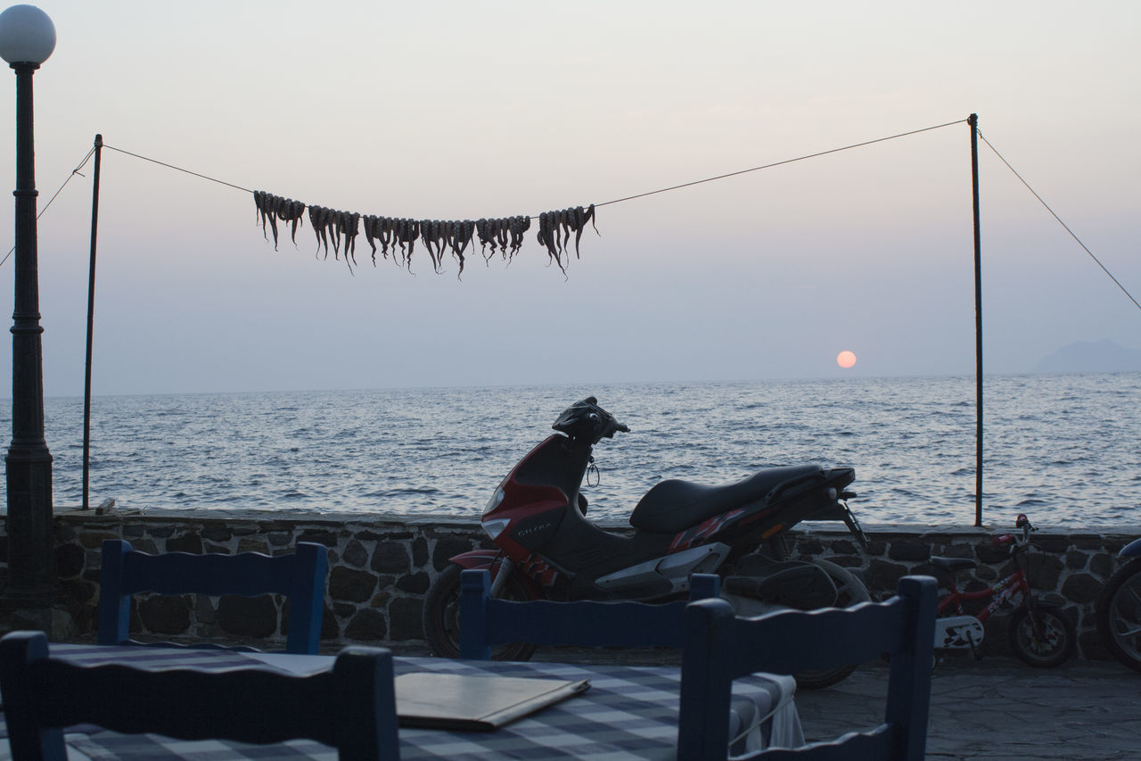 MEN SITTING ON TABLE BY SEA AGAINST CLEAR SKY DURING SUNSET