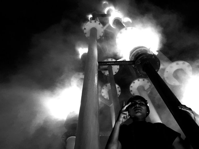 Low Angle View One Person Night Outdoors One Man Only Blackandwhite Real People Men Heat - Temperature Smoke - Physical Structure Illuminated Protective Mask - Workwear Sky People Adult Water Park