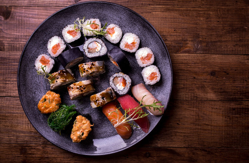 Sushi set nigiri and rolls served on brown wooden table background. Top view food photography. Copyspace for text and design elements Set Sushi Asian Food Choice Dinner Directly Above Food Food And Drink Freshness Healthy Eating Indoors  Japanese Food Meal No People Plate Ready-to-eat Rice Seafood Studio Shot Sushi Top View Variation Wellbeing Wood - Material