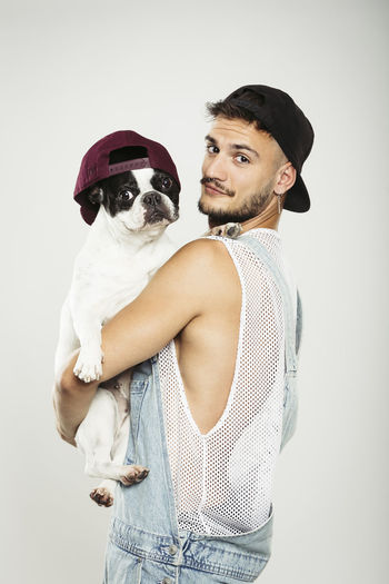 Earrings Hispter Modern Piercings Bulldog French Canine Cap Casual Clothing Casual Clothing Person Cut Out Dog Domestic Domestic Animals Handsome Hat Looking At Camera Mammal One Animal People Pet Owner Pets Portrait Shirt Studio Shot Young Men