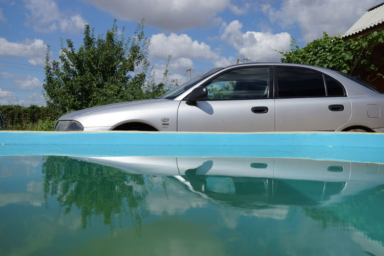 Reflection Car Tree No People Water Outdoors Cloud - Sky Tranquility Landscape Day Sky Branch Travel Destinations Vibrant Color Color Tree Dramatic Sky Cars Beauty Multi Colored Reflections In The Water Blue Sky Green Color Blue Sky And Clouds