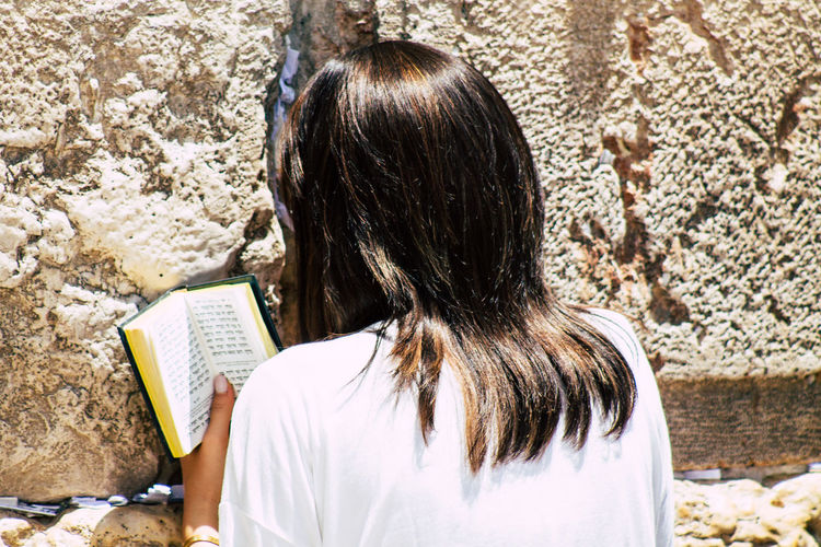 Rear view of woman with open book against wall