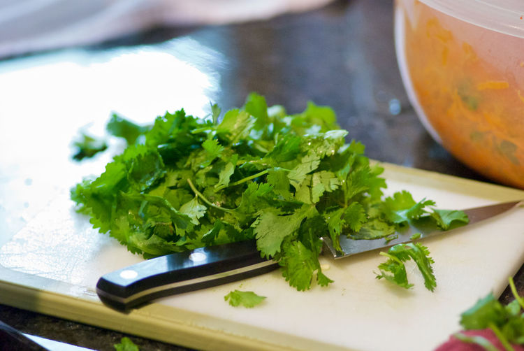 High angle view of coriander leaves and knife on cutting board