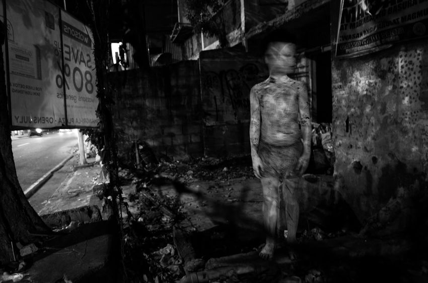 MANDALUYONG CITY, PH - This boy takes trick or treating to a whole new level. All painted in white with splattered red paint as blood, he portrays a creepy child ghost while out trick or treating in the streets with his friends. People Black And White Untold Stories Philippines Documentary Photography EyeEmBestPics Larrymonseratepiojo EyeEm Best Shots Eyeem Philippines The Human Condition Everybodystreet The Week On EyeEm Street Photography Filipino Haloween