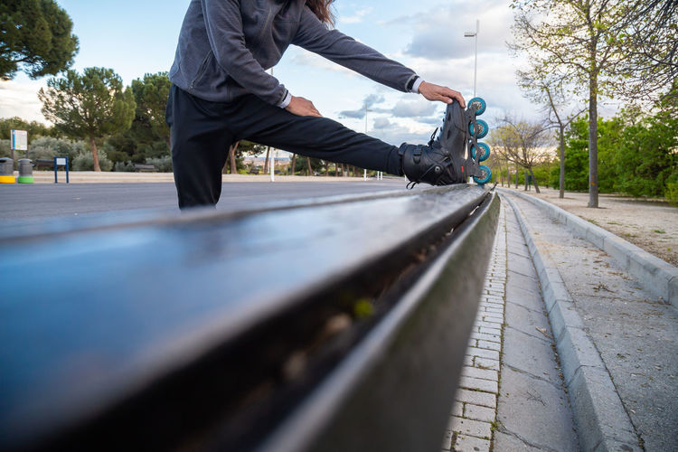 Low section of man skateboarding on road against sky