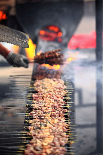 0093-Lamb skewers or kawaplar on a big old-fashioned metal charcoal grill getting roasted over smoke and embers in a local food stand at the Hotan's Sunday market. Xinjiang Uyghur Autonomous region-China. Heat - Temperature Burning Selective Focus Food Fire Flame Preparation  Smoke - Physical Structure Lamb Mutton Fat Meat Skewer Kebab Kawaplar Chuan Roasted Grilled Grill Charcoal Coal Ember Metal Metallic Traditional Old Fashioned Halal Brochette Roasting Jack Stick Sprinkled Spiced Cumin Pepper Hot Chili Street Food Food Stand Uyghur Cuisine Human Hand Cook  Bundle Sunday Market Chukubaza Bazaar Hotan City Xinjiang Uyghur Autonomous Region China