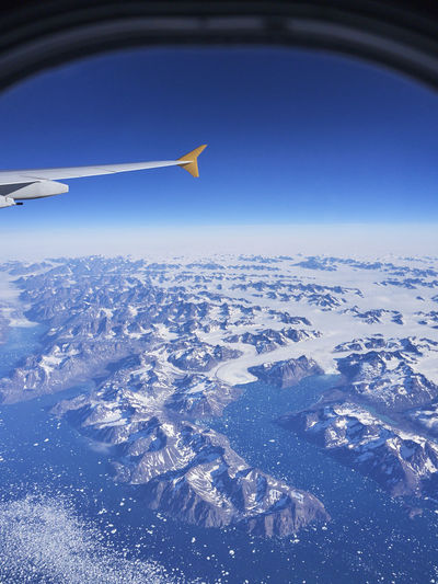 Aerial view of airplane flying over snowcapped landscape against blue sky