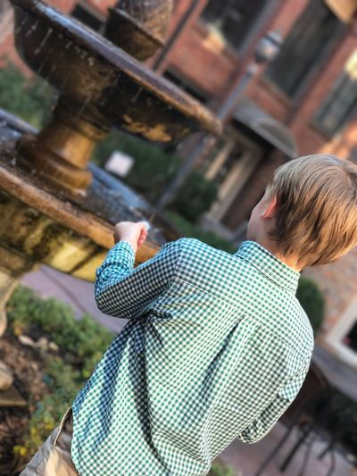 Rear view of boy holding coin while standing by fountain