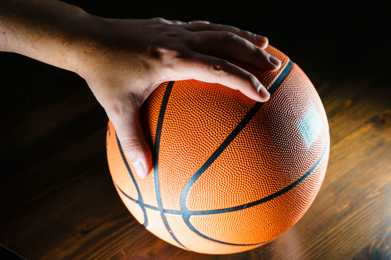 Cropped image of man holding basketball on floor in dark