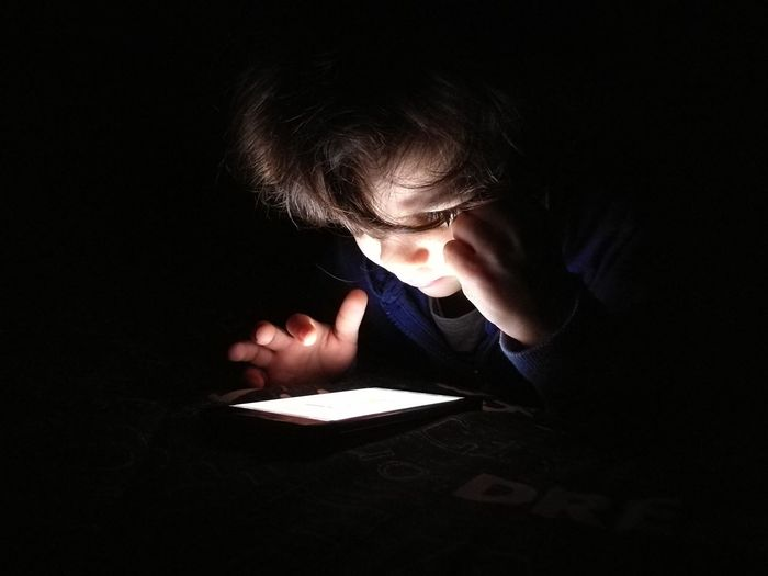 Close-Up Of Boy Using Digital Tablet In Darkroom