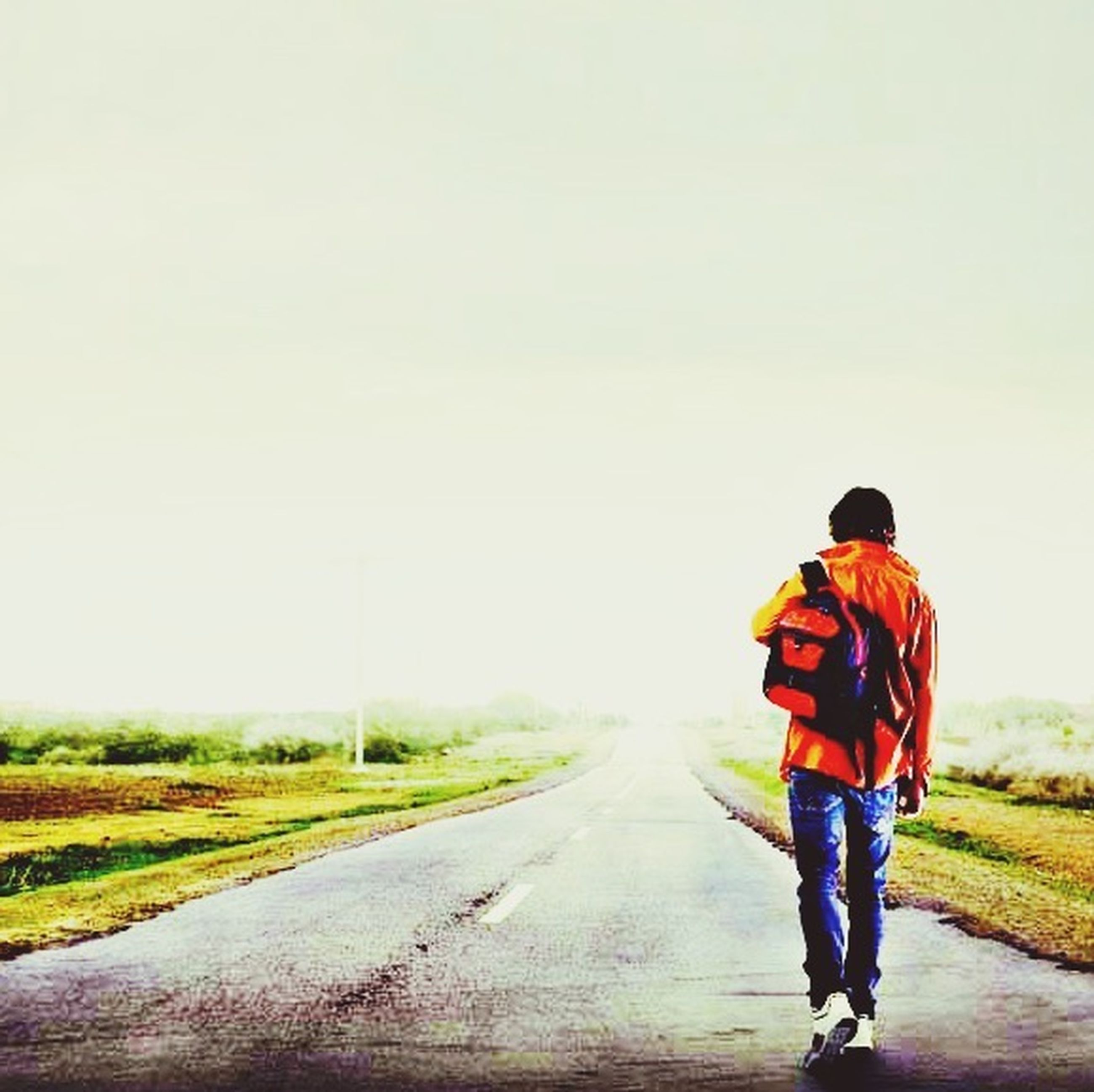 rear view, full length, clear sky, lifestyles, copy space, road, walking, leisure activity, men, the way forward, casual clothing, standing, transportation, country road, on the move, field, landscape, person