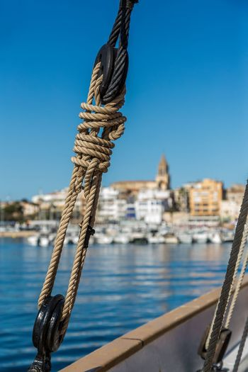 Close-up of rope tied to moored at harbor against clear sky