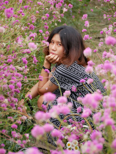 Happy woman standing by pink flowering plants
