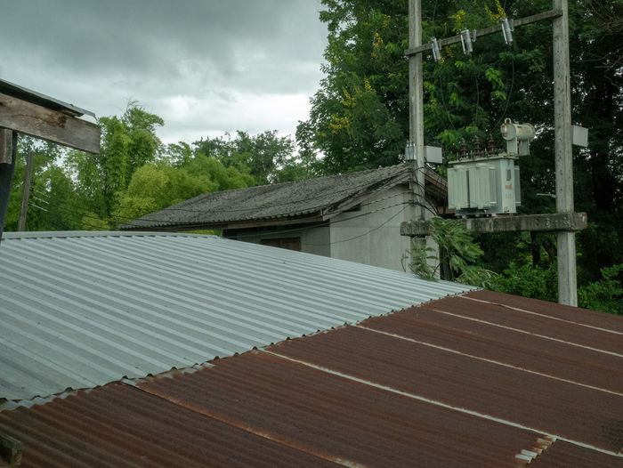 Tilt image of house roof and trees against sky